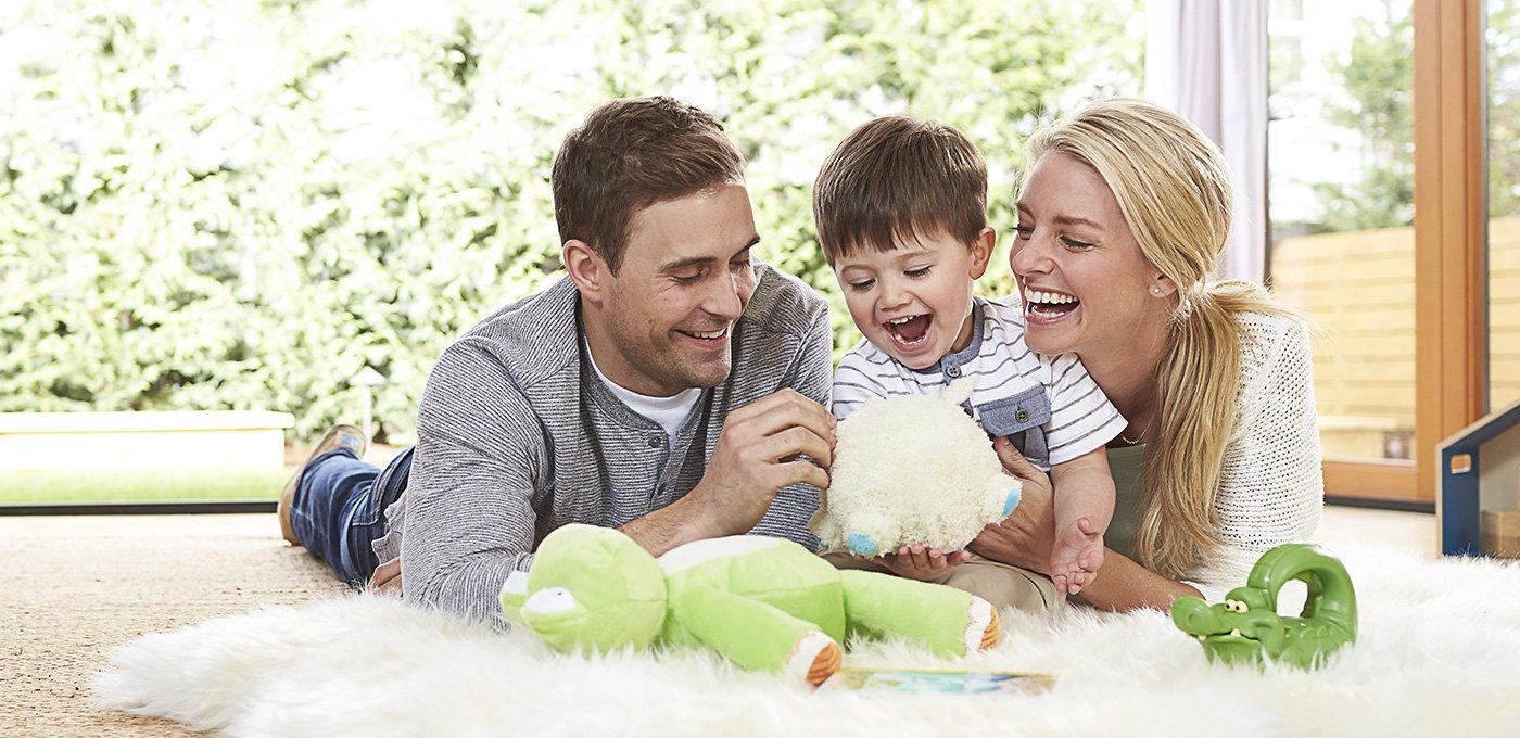 Cha và mẹ đang nằm chơi với con trai của họ và đấy là gia đình